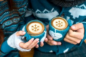 Couple holding knitted coffee cups dressed in sweater